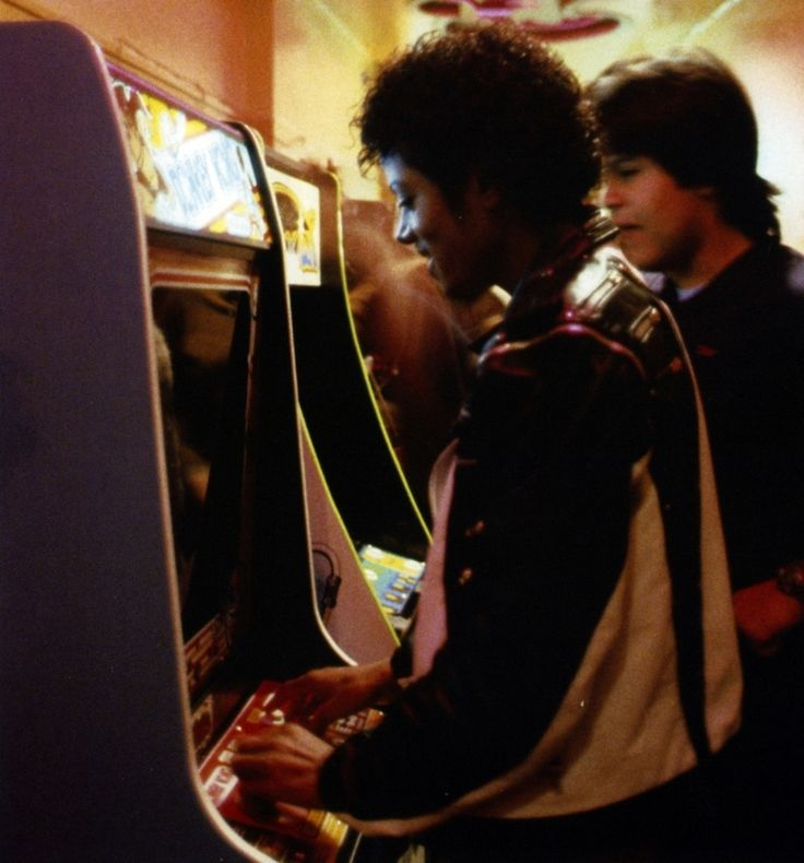 Two young men playing video games in an arcade